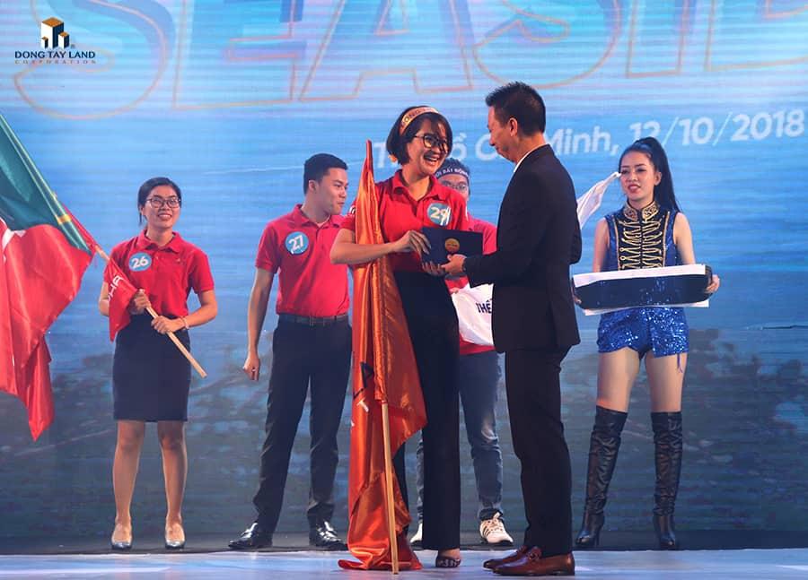 Ông Nguyễn Hữu Việt (Giám đốc Kinh doanh BĐS Nghỉ dưỡng - Tập đoàn Vingroup) trao phần thưởng giải nhất cho chị Hoàng Kim Ngọc (TPKD sàn giao dịch Đông Tây Land 5)